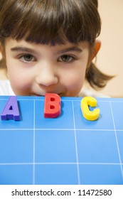 child learning the ABC's. The focus is on the mouth leaning on the blue board