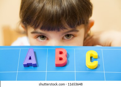 child learning the ABC's. The focus is on the letters
