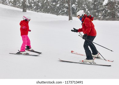 Child learning how to ski with an instructor. Winter sport