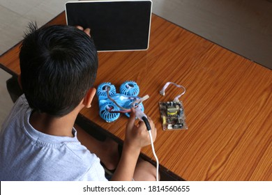 A child learning to make online electric drone. tab screen black. A child tabs that screen while zooming. concept online kids coding classes
