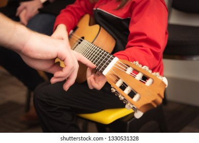 A child learning to play the guitar