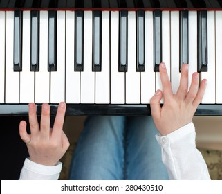 Child learning to play the piano. Top view.