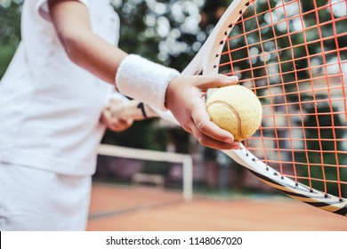 Child learning to play tennis in the sport club. Cropped image of a girl child preparing to serve tennis ball. Little girl tennis player with ball and racket on court. Active exercise for kids.