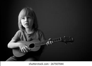 Child learning to play the ukulele