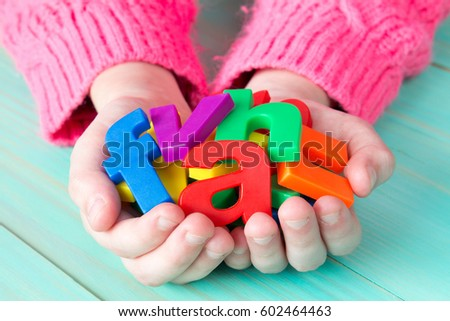 Child learning to read using magnetic letters. Education School  Concept