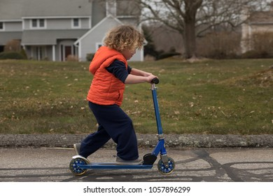 A child is learning to ride a scooter bike outside. He is wearing an orange vest.  The young child is going slow as he learns to ride the skateboard in the neighborhood with grass and houses.