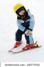 Child learning to ski in winter skiing resort practicing the correct moves.