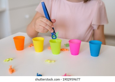 The child learns colors. A little girl sorts animal figures by color. Preschool education and development of children. The girl holds the tongs in her hands. Learn colors.