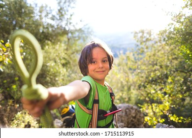 A child learns to knit the safety knot from the rope. Climbing rope and carabine for belaying. A little boy is trying to tie a knot. Scout training. Children's hands and safety rope. Teaching children