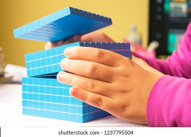 Child learns math volume and capacity. Child for learning model uses a three-dimensional cube. Plastic model cubic decimeter . Education concept.