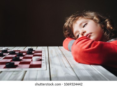 The child learns to play checkers. Intellectual development of the child. The child is tired. Copy space.