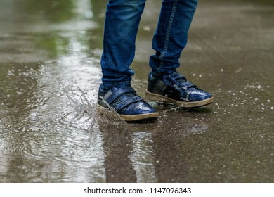 Child legs in sneakers close-up, the child jumps in puddles. Health, happy childhood concept.