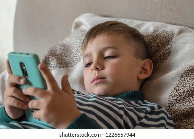 The child lies in bed and looks into the smartphone. The boy is bored, calls, e-mails, communicates, waits for his parents, searches for information, uses the gadget, sits on the Internet