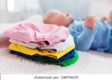 The child lies near a stack of multi-colored reusable diapers on a changing table