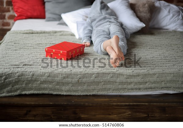 The child lies on the big bed with his face buried in the pillow. Nearby there is a bright red box with a gift. Child isn't happy. He is disappointed with a gift and doesn't want to look at this gift