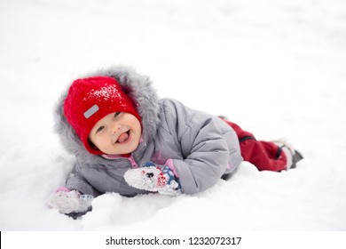 Child lies in the snow and shows tongue.