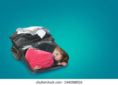 A child lies in a suitcase in which things are folded. Concept of travel and styling of things and clothes. On a blue background.