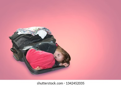 A child lies in a suitcase in which things are folded. Concept of travel and styling of things and clothes. On a pink background.