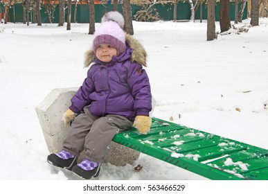 Child in lilac winter clothes sitting on a green bench in snow