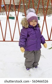 Child in lilac winter clothes standing in snow near a lattice