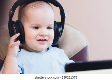 child listening to music on headphones at home