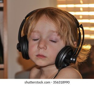 Child listens to music in headphones at bright spring evening