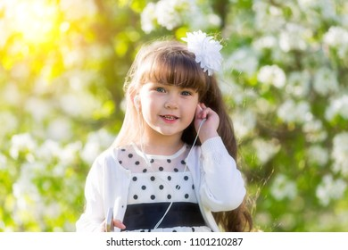 The child listens to music on headphones. The girl 4-5 years has brought an audio earpiece from phone to ear.