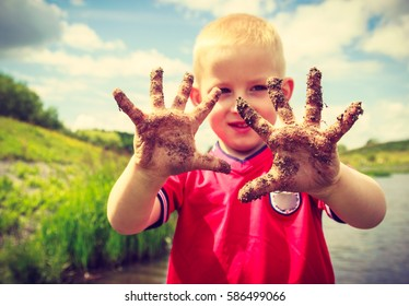 Child little blonde boy kid playing outdoor showing dirty muddy hands. Happy childhood.