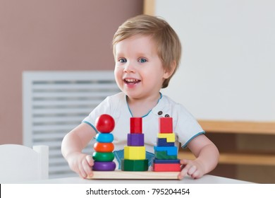 child little boy playing wooden toy pyramid himself at home or kindergarten. early development of children