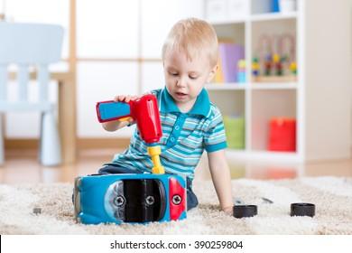 Child little boy repairs toy car indoor