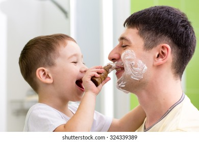 Child little boy shaving his father in bathroom
