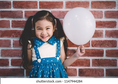 child little cute girl smile and have fun in the party with white balloon.