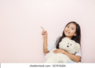 Child little girl asian thai nationality with white toy teddy bear over pink wall background pointing to corner.