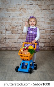 The child, a little girl with a cart full of vegetables and fruits. Purchase of products in the supermarket.