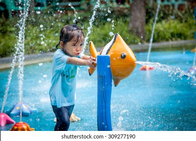 Child little girl having fun to play with water in park fountain in summer time
