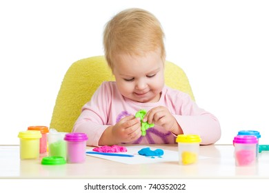 Child little girl learning to use colorful play dough isolated on white background