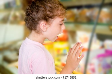 child little girl looking in food shop display excited with sweets