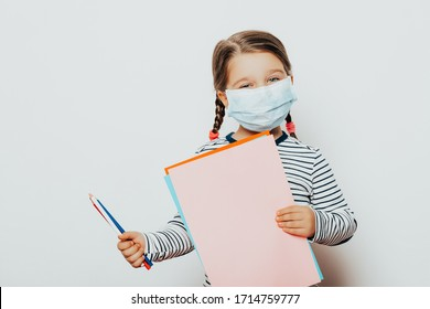 child little girl in medical mask is sitting at home in quarantine. education. kid with pencils and colored paper. Entertainment for the  children during quarantine. Self isolation.