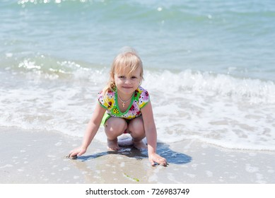 A child, a little girl playing fun on the seashore in the summer.
