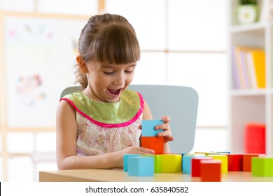 child little girl playing with wooden toys at home or kindergarten