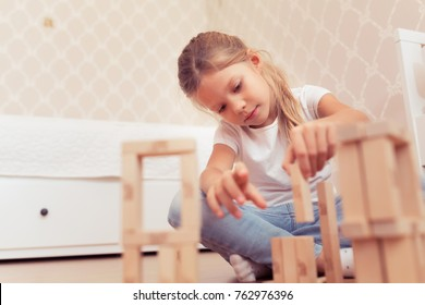Child little girl playing with wooden blocks the unstable tower