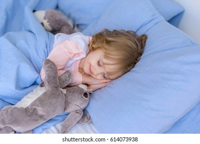 child, little girl sleeping in bed with toy rabbit. Concept of the happy babies.
