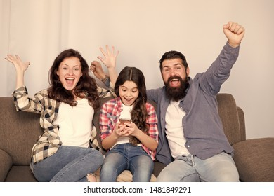 Child little girl use smartphone with parents. Friendly family having fun together. Mom dad and busy daughter relaxing on couch. Family leisure. Parental advisory. Family spend weekend together.