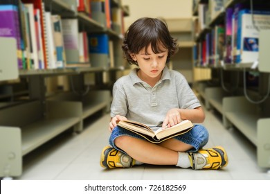 child little youth study read book in library, Youth student in classroom , Young kid point to book with book shelf, Education thinking textbook concept.