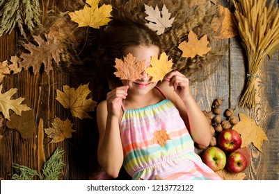 Child with long hair with fallen maple leaves. Fall nature gifts. Autumn coziness is just around. Tips for turning fall into best season. Kid girl smiling face lay wooden background fall attributes.
