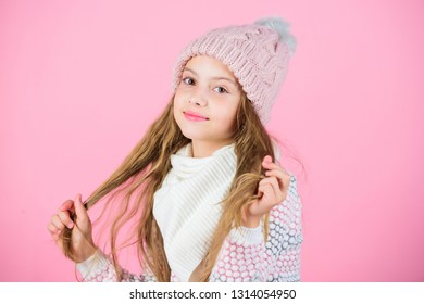 Child long hair smiling. Girl wear knitted hat pink background. Prevent winter hair damage. Winter hair care tips you should definitely follow. Winter time train yourself to go longer between washes.