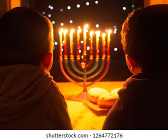 A child looking at Hanukkah candles. It is a Jewish custom to light candles on the 8 days of Hanuka celebrating the miraculous victory over the ancient Greeks during the Second Temple period.