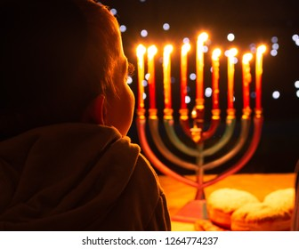A child looking at Hanukkah candles. It is a Jewish custom to light candles on the 8 days of Hanukkah celebrating the miraculous victory over the ancient Greeks during the Second Temple period.