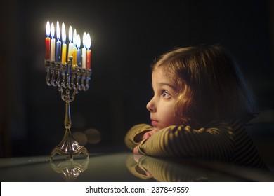 Child Looking at Menorah Candles