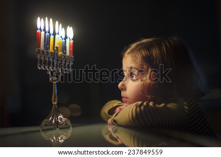 Child Looking at Menorah Candles